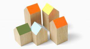 Houten blokjes in de vorm van een huisje met gekleurde schuine daken in een groepje bij elkaar