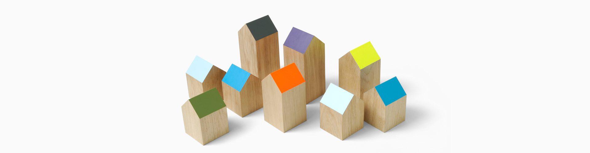 Houten blokjes in de vorm van een huisje met gekleurde schuine daken