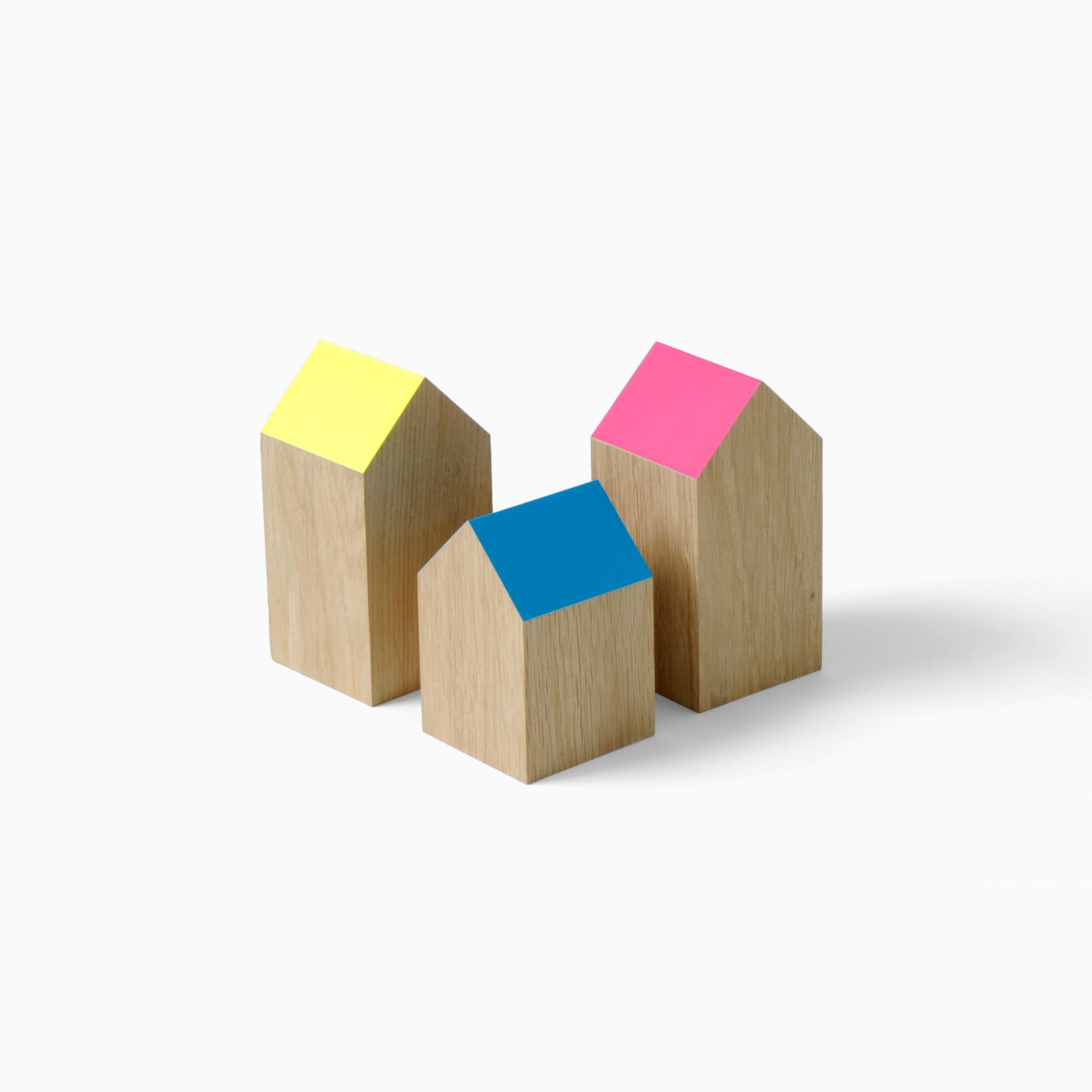 Drie houten blokjes in de vorm van een huisje met schuine daken gekleurd in roze, blauw en geel